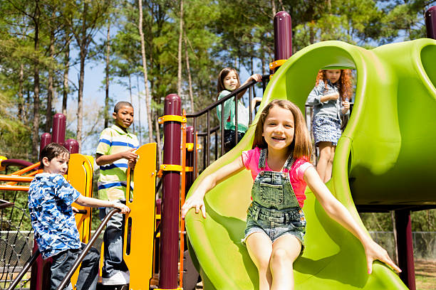 elementary children play at school recess or park on playground. - sliding stock photos and pictures