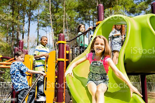 Elementary Children Play At School Recess Or Park On Playground Stock Photo - Download Image Now