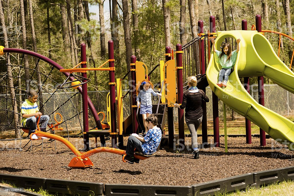 Elementary children play at school recess or park on playground. stock photo