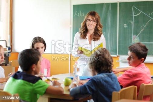 istock Elementary classroom setting. Focus on teacher and chalkboard. 474238183