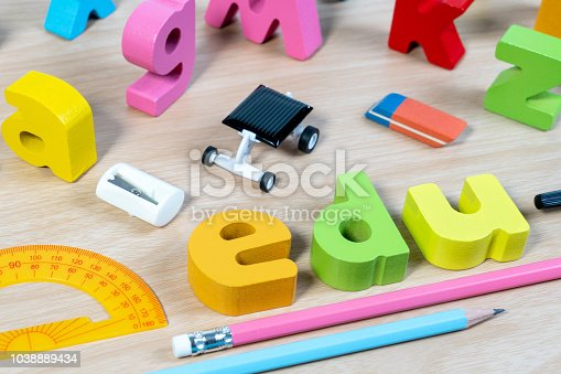 istock Elementary classroom table with wooden word EDU and education supplies for school background. 1038889434