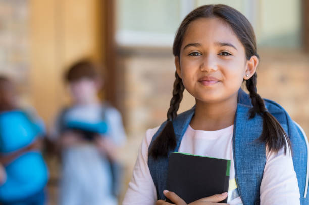 Elementary girl at school Smiling student girl wearing school backpack and holding exercise book. Portrait of happy asian young girl outside the primary school. Closeup face of smiling hispanic schoolgirl looking at camera. 8 9 years stock pictures, royalty-free photos & images