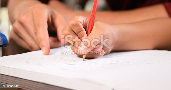 istock Elementary Girl Doing Homework Hand Writing On Exercise Book 821264312