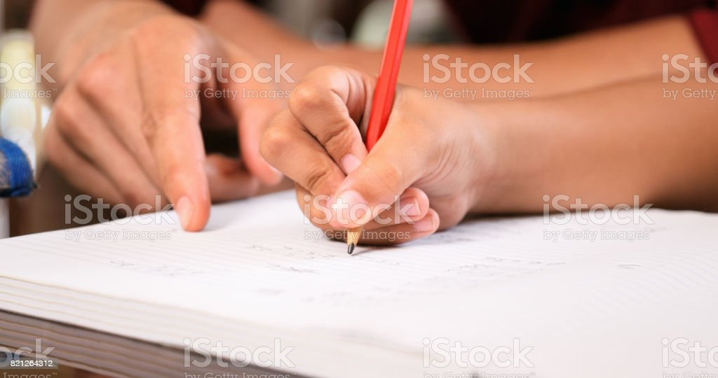 Elementary Girl Doing Homework Hand Writing On Exercise Book stock photo