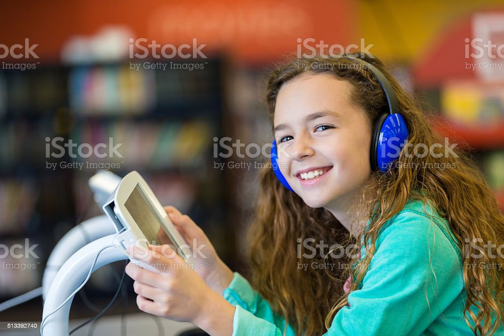 Elementary girl using digital tablet and headphones in modern library stock photo