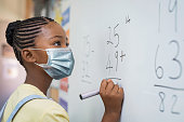 istock Elementary girl wearing protective face mask at school 1275847596