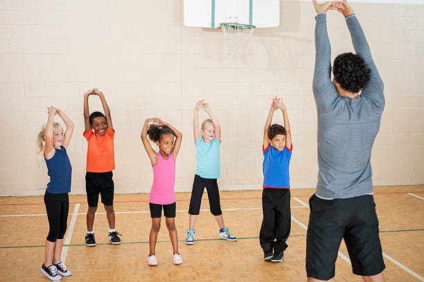 Elementary Kids Stretching in Gym Class stock photo