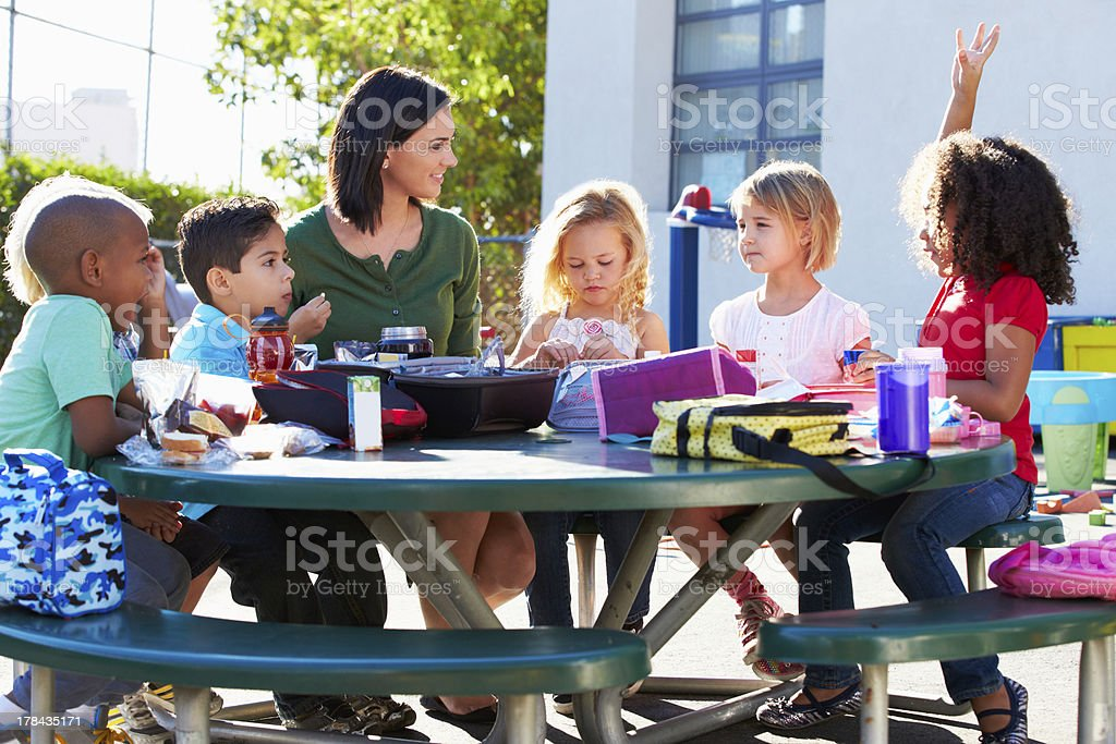 Elementary pupils and teacher eating lunch at green table royalty-free stock photo
