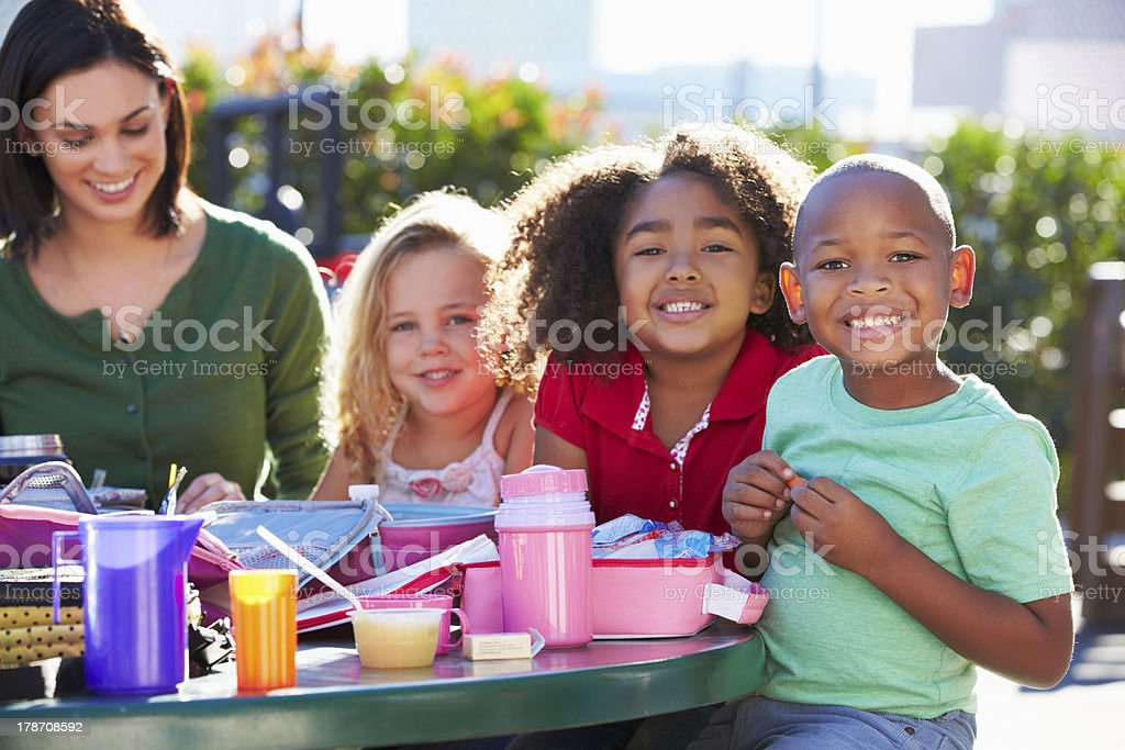 Elementary pupils and teacher eating lunch in the park royalty-free stock photo