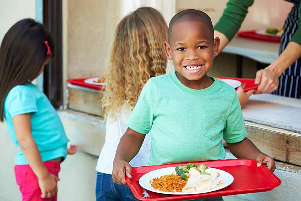 elementare schüler sie die gesunde mittagessen in der cafeteria serviert. - kantine stock-fotos und bilder