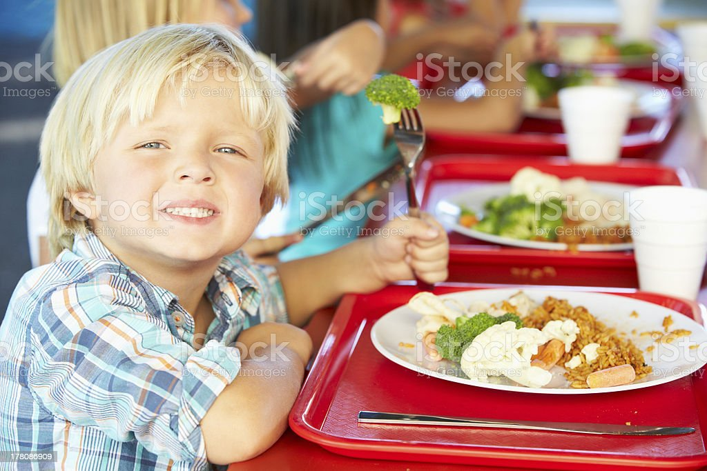 Elementary pupils Having a Balanced Diet in their Cafeteria  stock photo