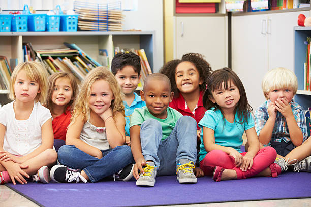 elementary pupils sitting on the floor in a classroom - elementary age stock photos and pictures