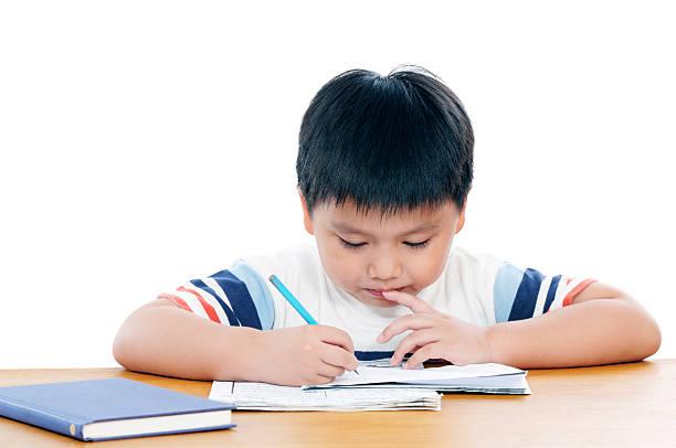Grundschule junge seine Hausaufgaben machen – Foto