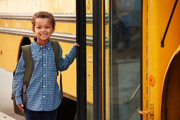 escuela primaria chico llegar un un autobús escolar - autobuses escolares fotografías e imágenes de stock