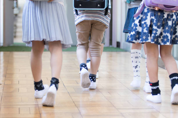 Elementary school children carrying bag stock photo