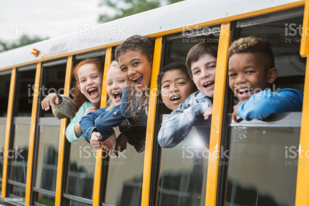 Elementary school children looking out window of bus stock photo