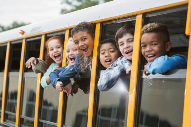 elementary school children looking out window of bus - school buses stock pictures, royalty-free photos & images