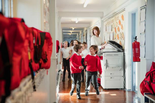 la escuela primaria los niños corriendo por el pasillo - regreso a clases fotografías e imágenes de stock