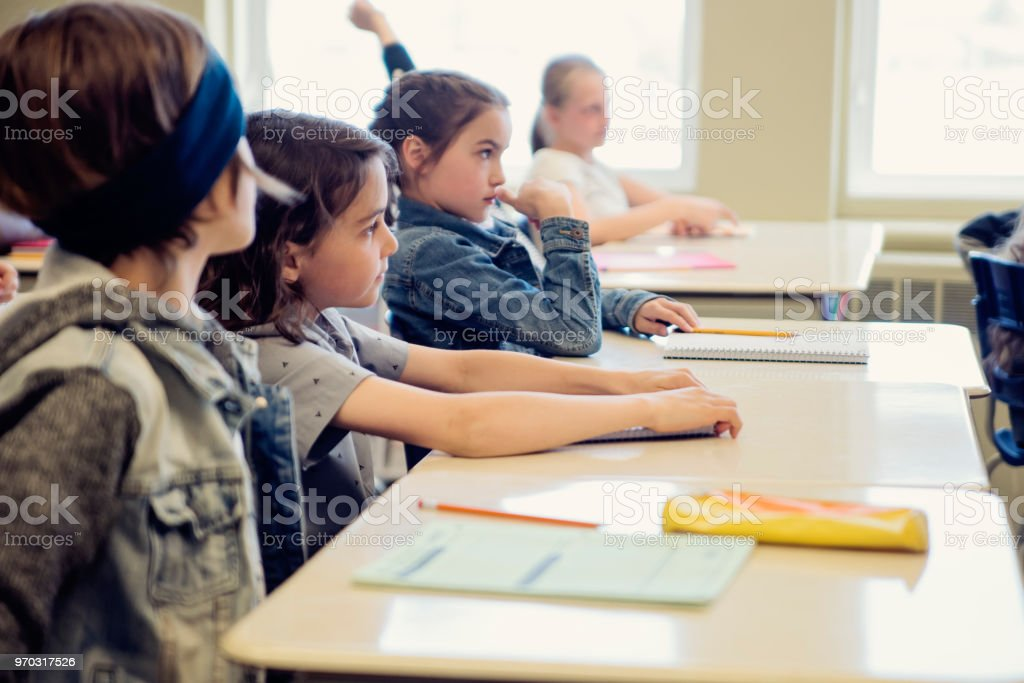 Elementary school children sitting and listening in classroom. royalty-free stock photo