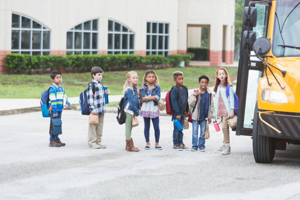 niños esperando el autobús fuera - autobuses escolares fotografías e imágenes de stock