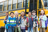 A group of seven multi-ethnic elementary school children, 7 to 9 years old, standing outside a yellow school bus, carrying backpacks.