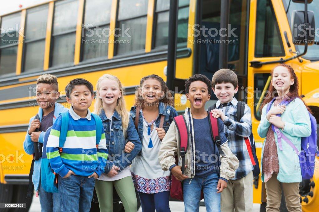 Elementary school children waiting outside bus stock photo