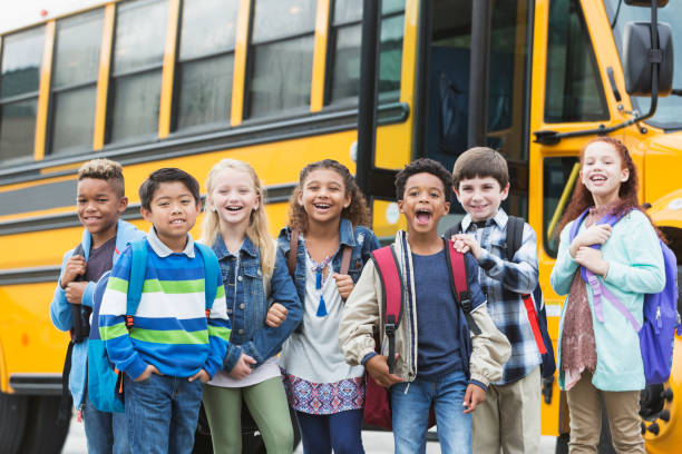 elementary school children waiting outside bus - back to school stock photos and pictures