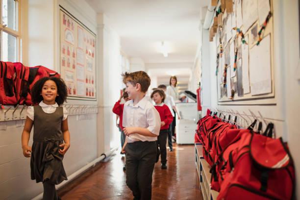 la escuela primaria los niños caminando por el pasillo - regreso a clases fotografías e imágenes de stock