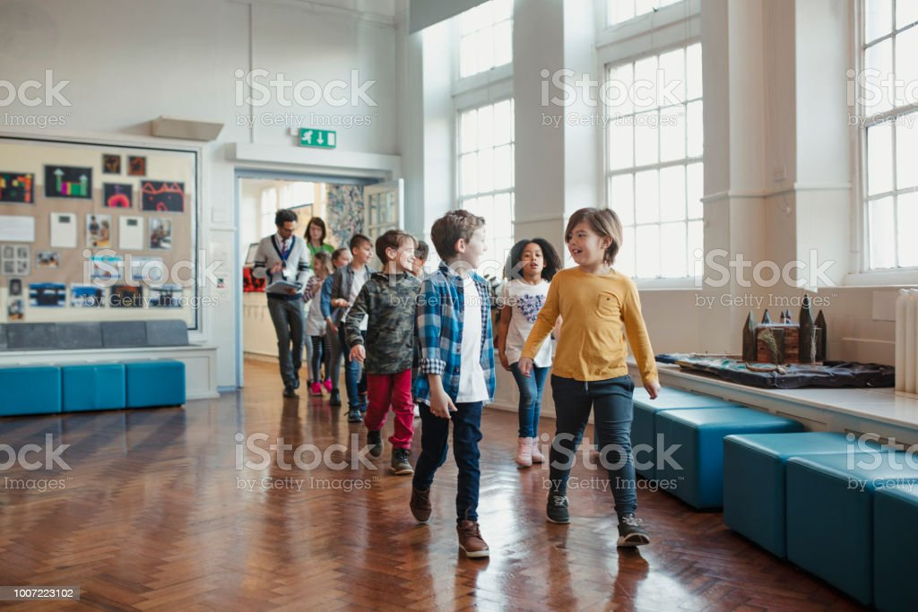 La escuela primaria los niños caminando por el pasillo - foto de stock