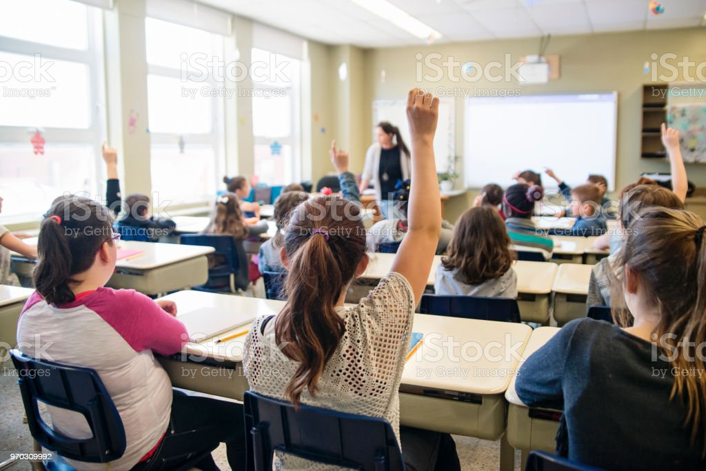 Elementary school children with arms raised in classroom. royalty-free stock photo