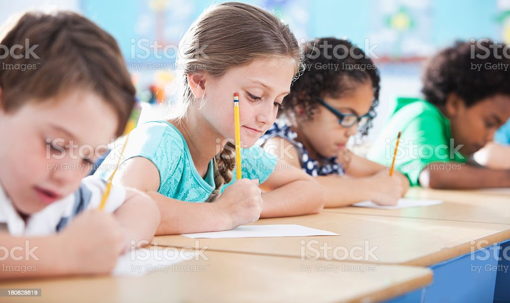 Elementary school children writing in class stock photo