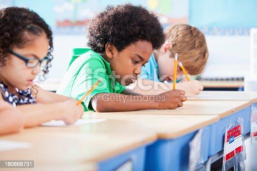 Multi-ethnic elementary school children writing in classroom.  Focus on African American boy (8-9 years).