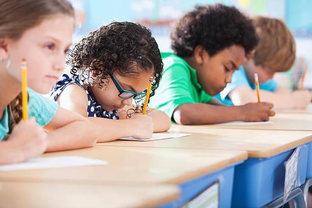 crianças na escola primária de classe escrevendo - aula de redação - fotografias e filmes do acervo