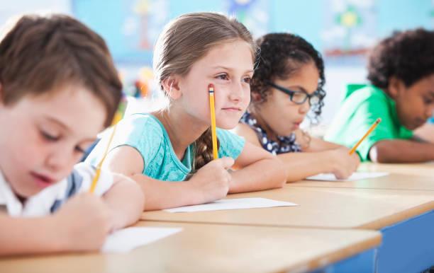 grundschule kinder schreiben in klasse - grundschule stock-fotos und bilder