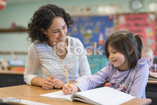 A young girl  cheerfully writes in her spelling workbook at her desk. Her teacher is kneeling beside the desk and encouraging her.