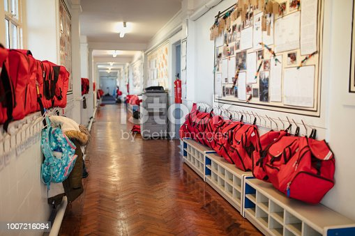 A corridor can be seen in a school where backpacks are hung in a row against the wall. This is a school in Hexham, Northumberland in north eastern England.