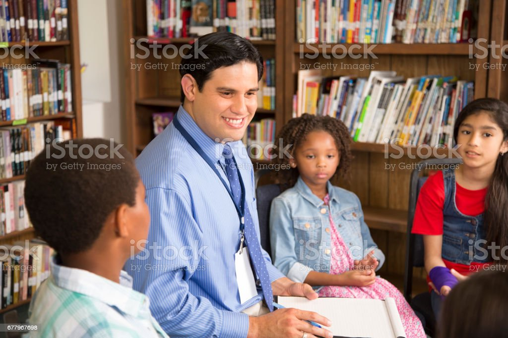Elementary school counselor with students in library. royalty-free stock photo