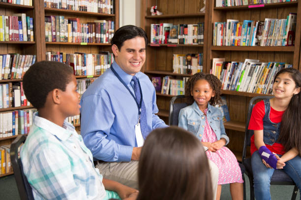 elementary school counselor with students in library. - school counselor stock pictures, royalty-free photos & images