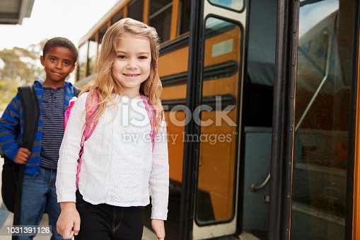 1031397608 istock photo Elementary school girl and boy waiting to board the school bus 1031391126