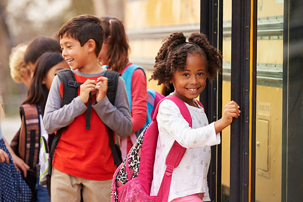 elementary school girl at the front of the school bus queue - school bus stock photos and pictures