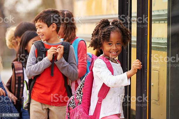 Elementary School Girl At The Front Of The School Bus Queue Stock Photo - Download Image Now