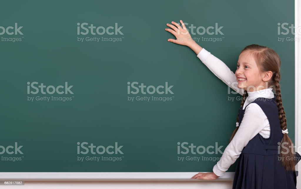 elementary school girl put hands on chalkboard background and show blank space, dressed in classic black suit, group pupil, education concept royalty-free stock photo