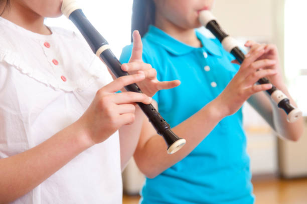 elementary school girls blow the recorder - recorder stock photos and pictures