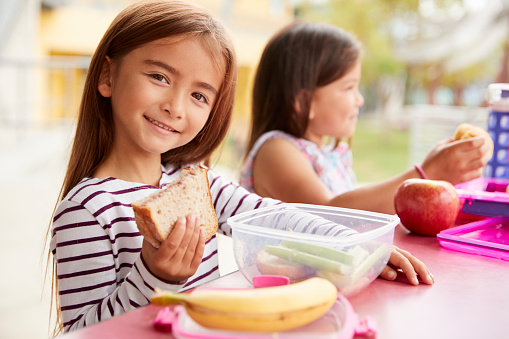 istock Elementary school girls eating at school lunch table 1031378086