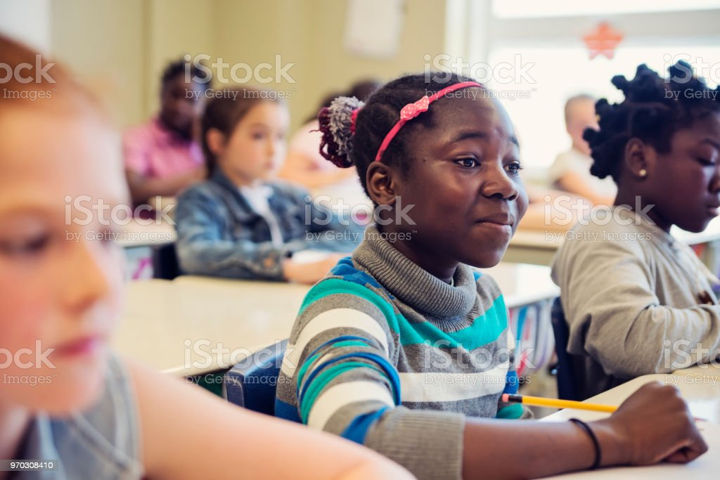 Elementary school girls sitting and listening in classroom. royalty-free stock photo