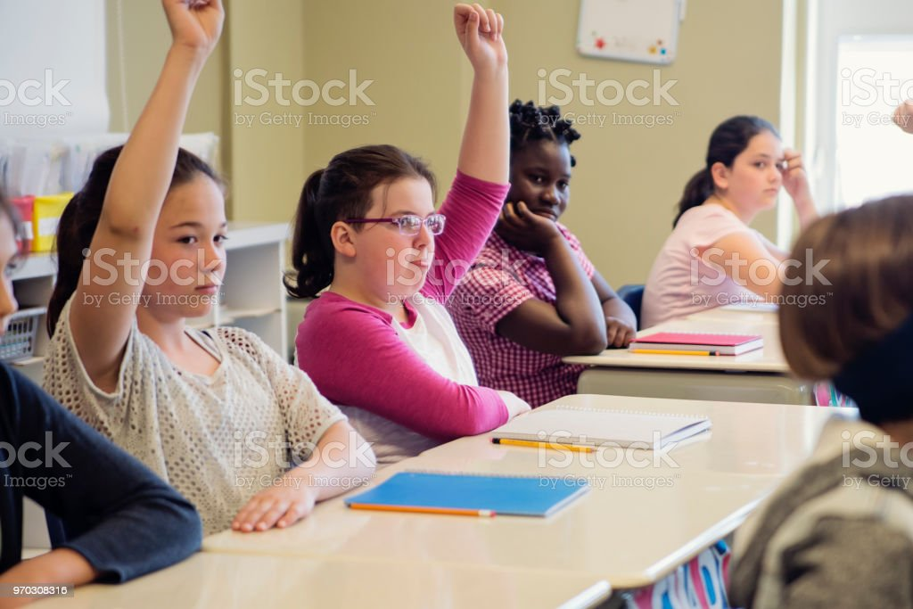 Elementary school girls with arms raised in classroom. royalty-free stock photo