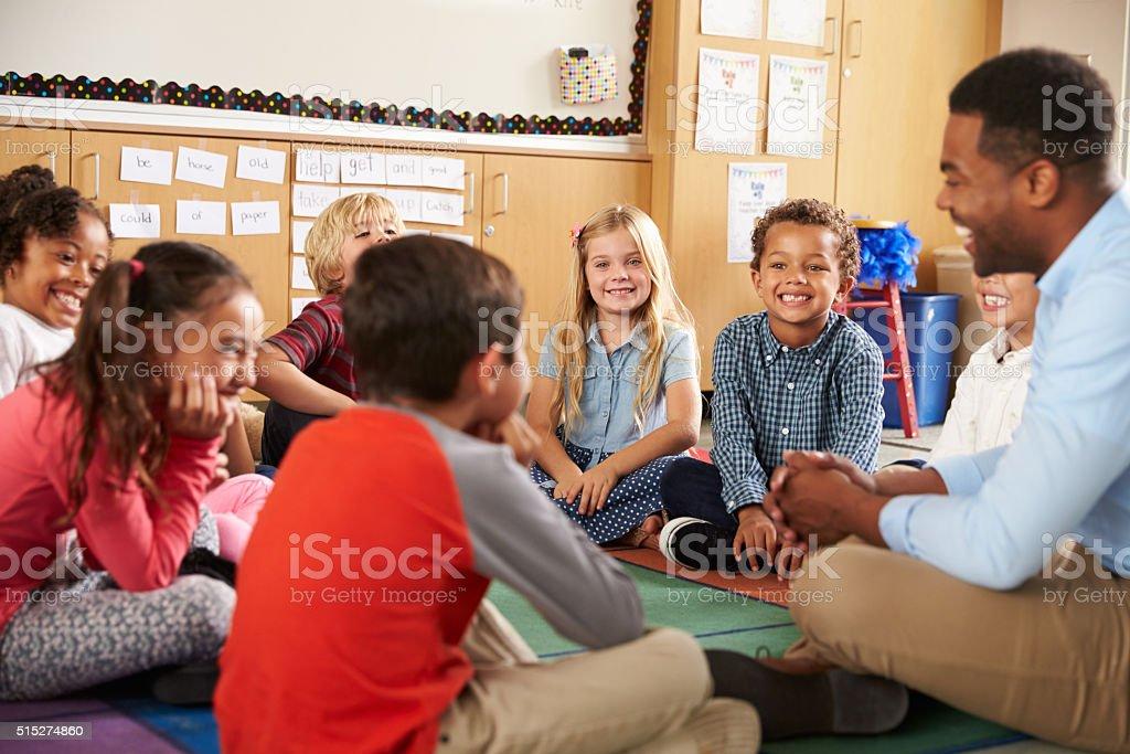 Elementary school kids and teacher sit cross legged on floor stock photo