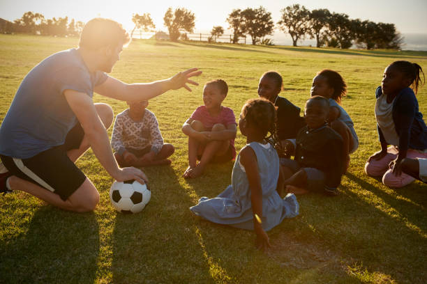 Elementary school kids and teacher sitting with ball in field stock photo