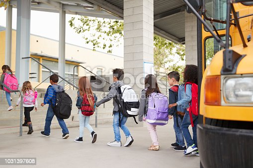 1031397608 istock photo Elementary school kids arrive at school from the school bus 1031397608