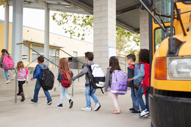 elementary school kids arrive at school from the school bus - school building stock pictures, royalty-free photos & images